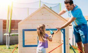 vader en dochter zetten een houten speelhuisje in elkaar